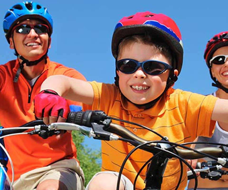 Kid in sunglasses riding a bike with his parents
