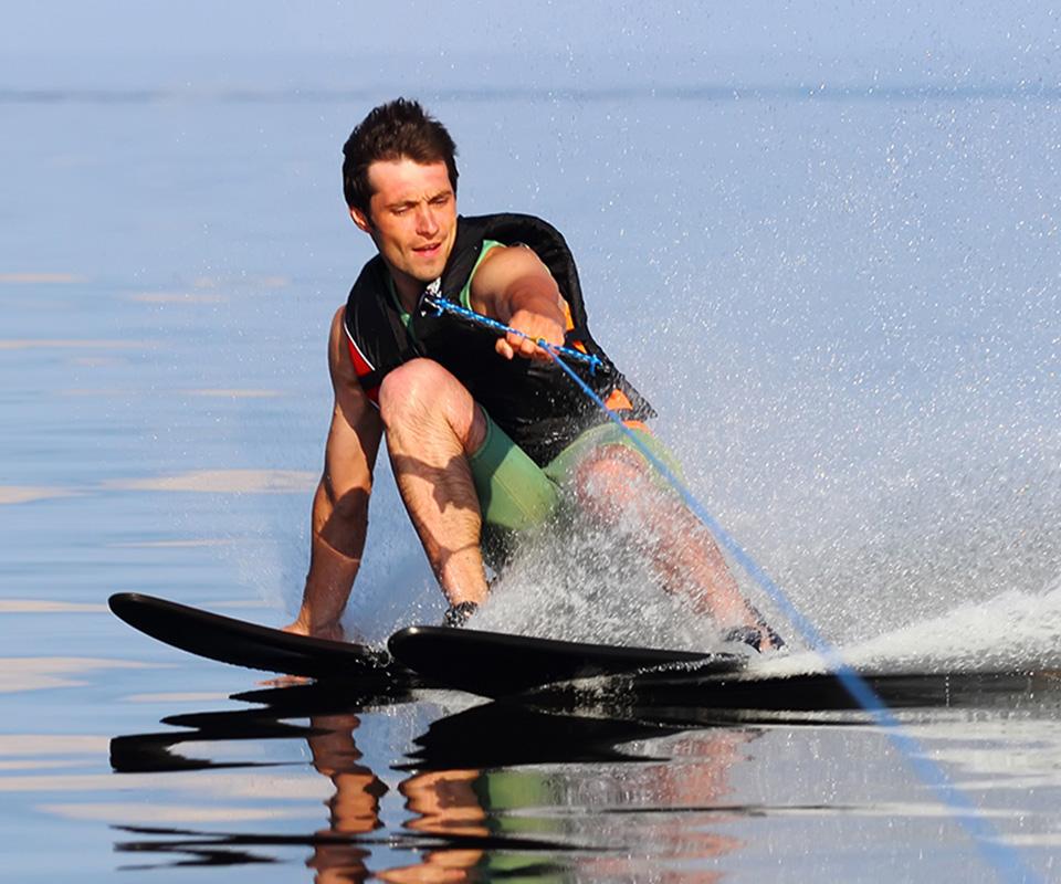 Guy water skiing in black life jacket