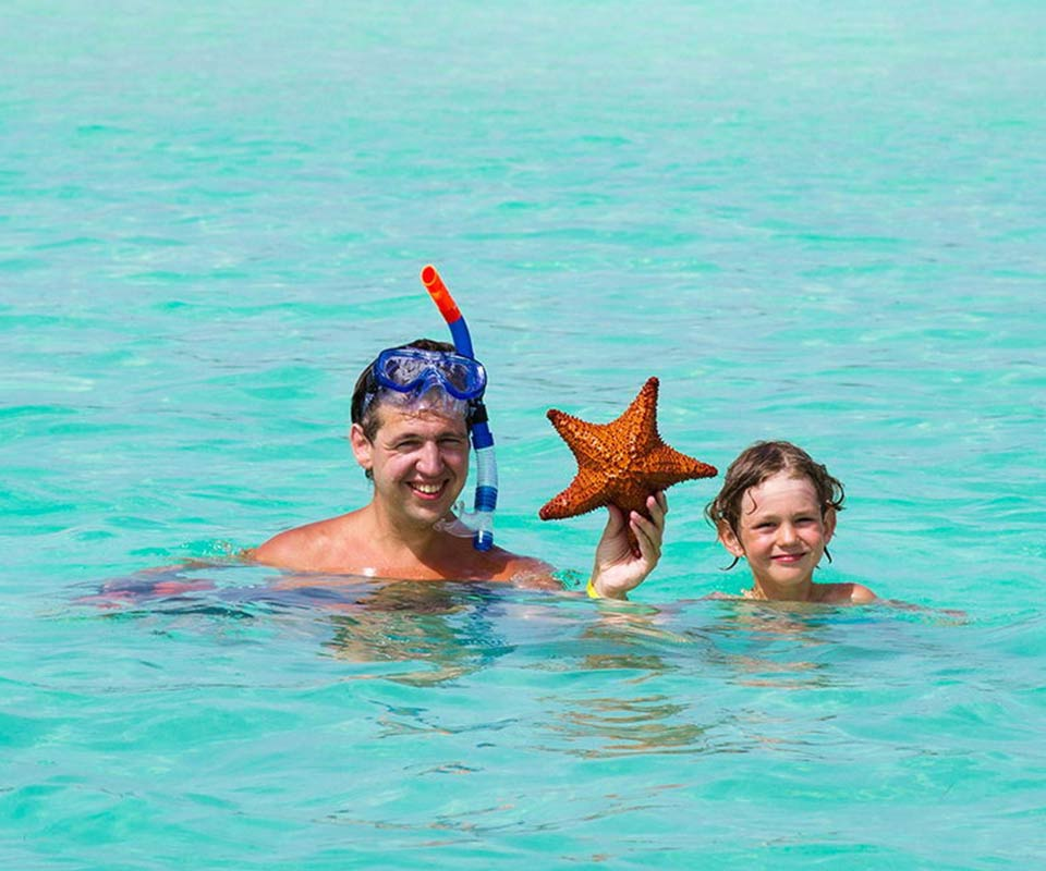 Father and son holding a starfish in crystal blue water