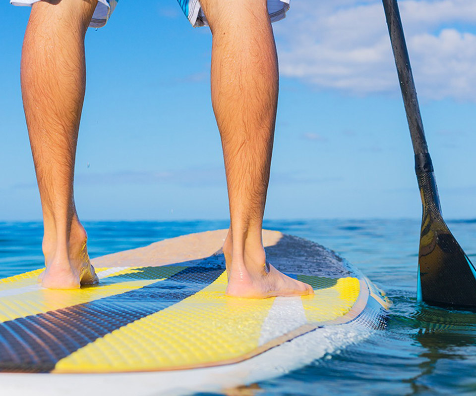 Guys legs and feet on a paddle board