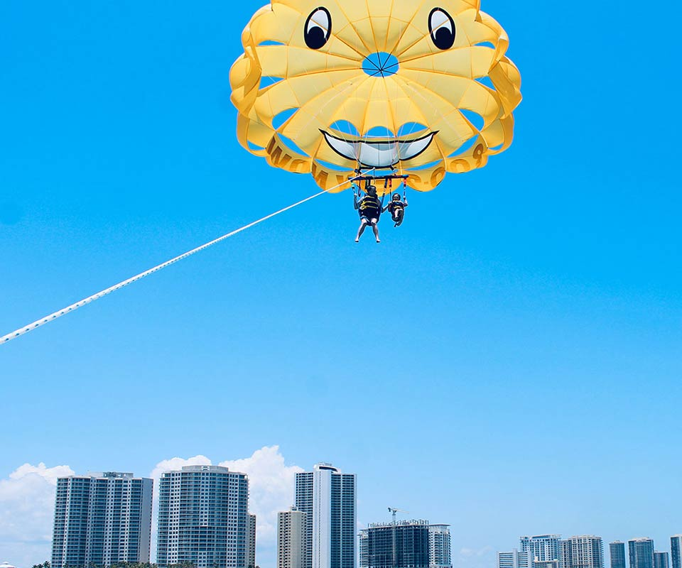 Tandem in yellow parasailing over Palm Beach