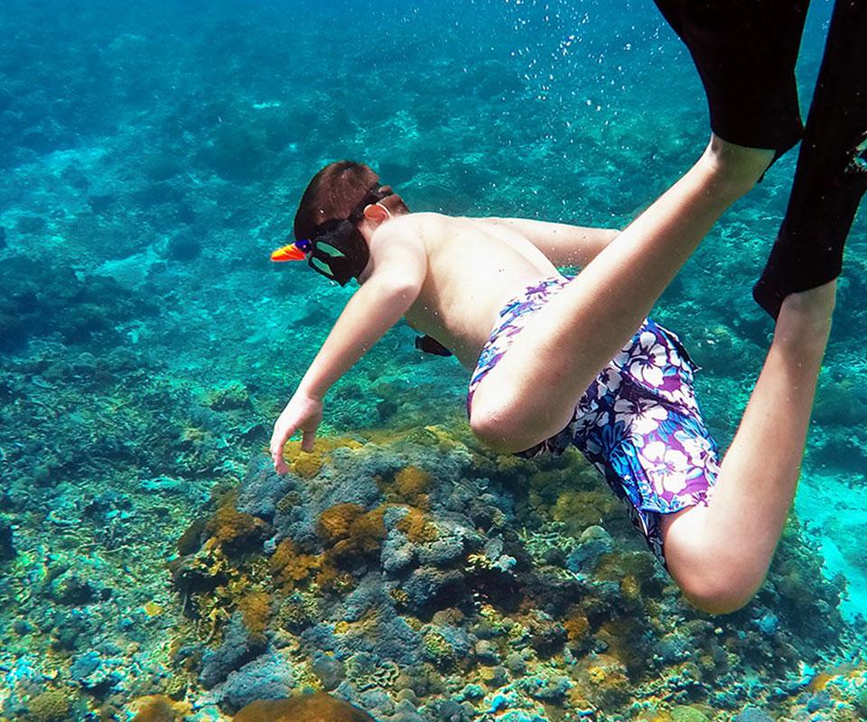 Kid snorkeling in clear water
