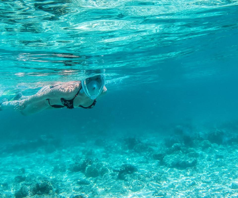 Girl in black swimsuit snorkeling