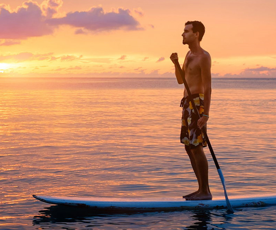 Dude paddleboarding with the sun setting over the ocean
