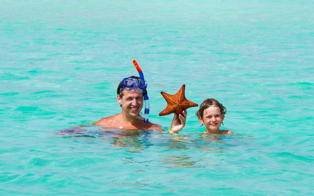 Father and son holding starfish
