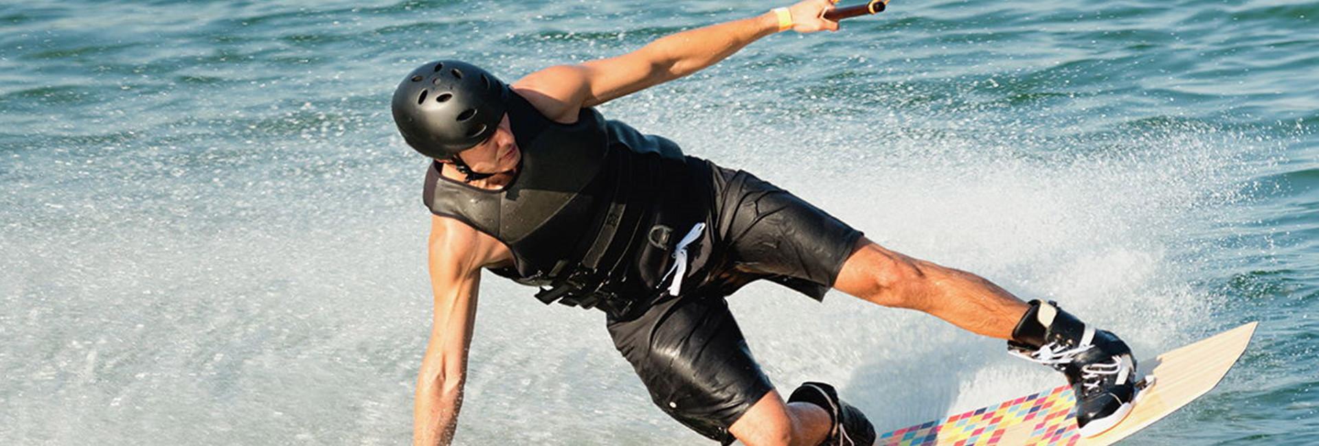 Dude in black wetsuit wakeboarding